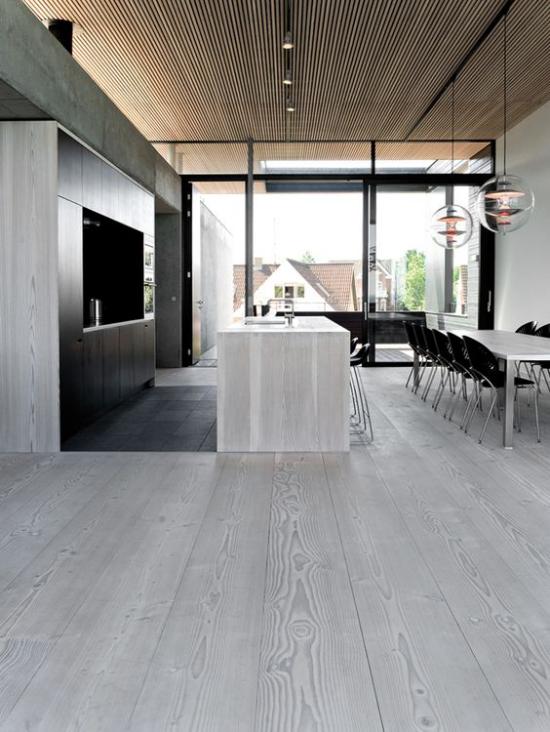 grauer Boden geräumige sehr moderne Küche mit Kücheninsel Esstisch Essecke daneben sehr schlichte Raumgestaltung