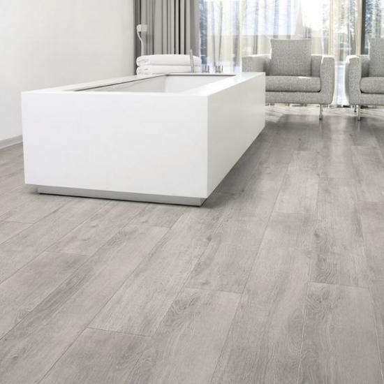 grauer Boden graues Holz im modernen Bad weiße Badewanne zwei Sessel hand-und Badetücher