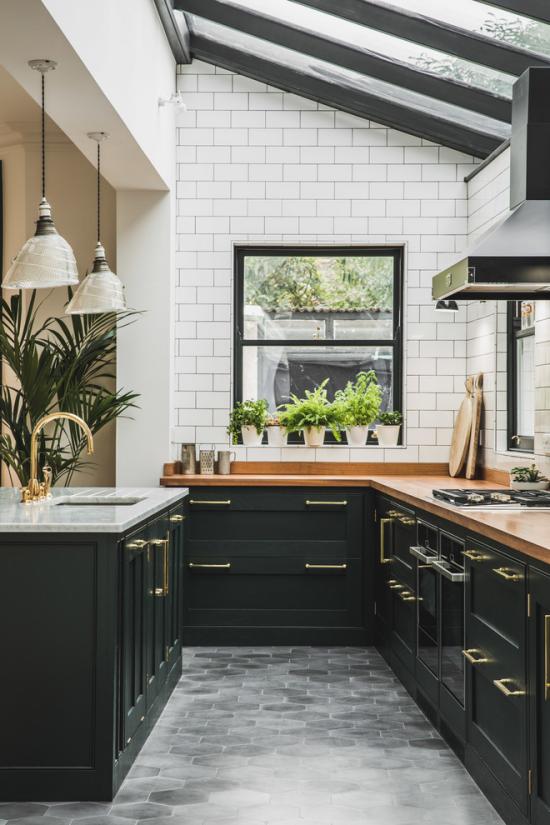 grauer Boden klassische Küche schwarze Schränke weiße Fliesen an der Wand graue Bodenfliesen etwas Grün