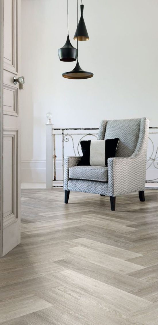 grauer Boden offenes Wohnzimmer minimalistische Einrichtung Laminatboden Fischgrätenmuster