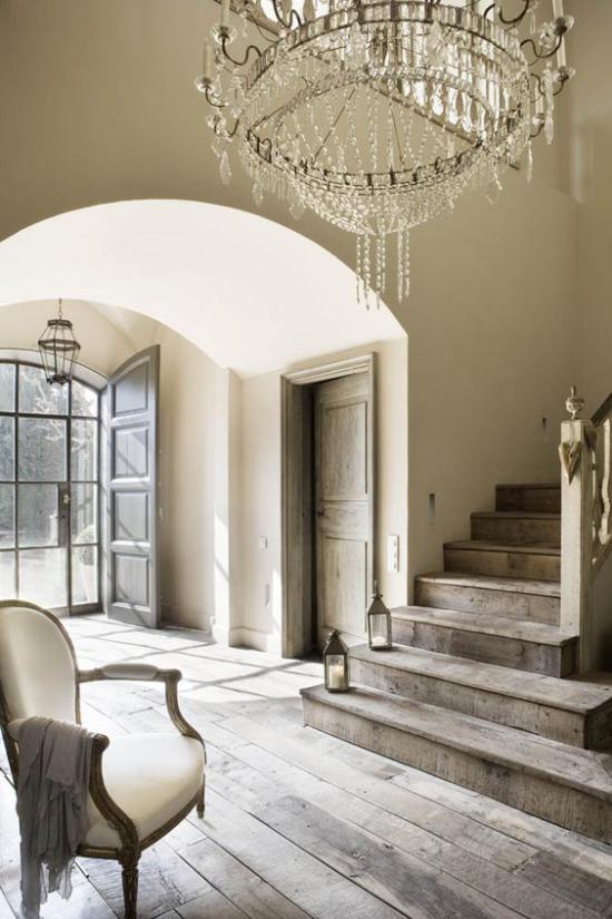 grauer Boden weiß getünchte Dielen im Eingangsbereich viel Licht Sessel Treppe zwei Kerzen