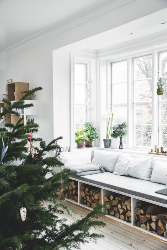 Erkerfenster Sitzecke am Fenster Holzaufbewahrung darunter Winterlandschaft draußen Tannenbaum im Vordergrund