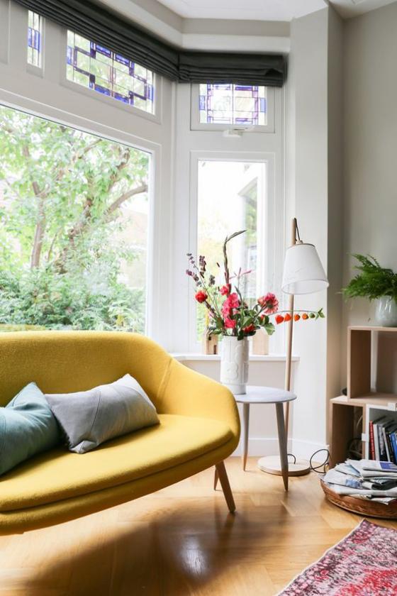 Erkerfenster Wohnzimmer gelbes Sofa Kissen kleiner Tisch Vase mit Blumen Bücherregal Teppich