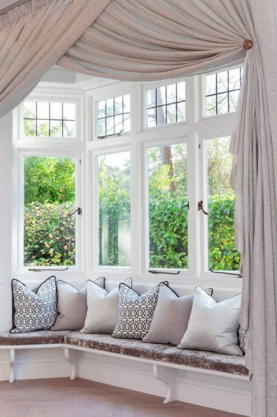 Erkerfenster Wohnzimmer gemütliche Sitzecke vor dem Fenster gestalten viele Wurfkissen Gardinen
