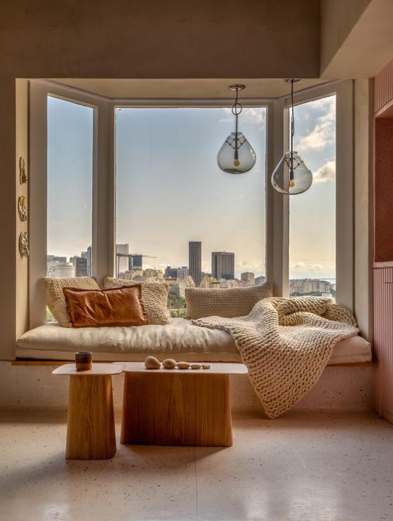 Erkerfenster herrliches Wohnambiente Sitzecke in warmen Farbtönen zwei kleine Tische viele Kissen Wurfdecke schönes Panoramabild auf eine Großstadt