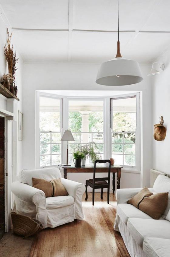 Erkerfenster im Home Office Vintage Sitzgarnitur mit weißen Überhüllen Schreibtisch vor dem Fenster