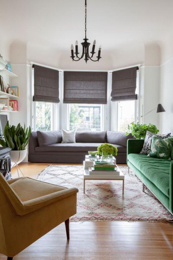 Erkerfenster im Wohnzimmer zusätzliche Wohnfläche dunkle Faltrollos bequeme Sofas Sessel Teppich grüne Zimmerpflanzen