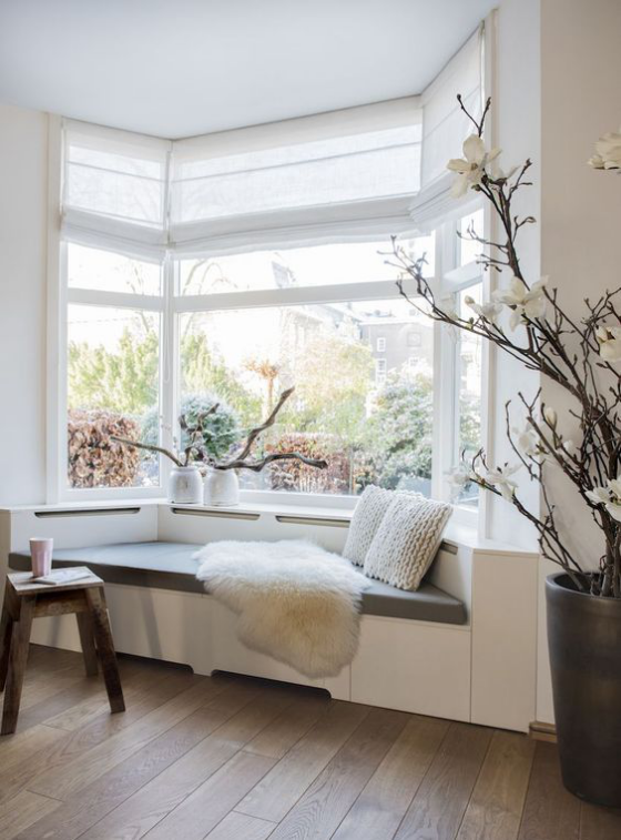Erkerfenster kuschelige Sitzecke Schaffell Kissen Deko aus Naturmaterialien