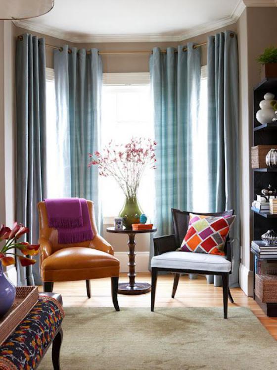 Erkerfenster schön eingerichtetes Wohnzimmer leichte blaue Gardinen Ledersessel bunte Raumgestaltung