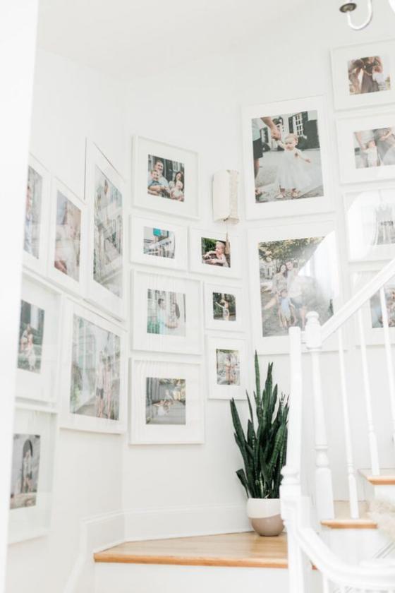 Fotowand im Treppenhaus in der Ecke schöne großformatige Bilder in weißen Rahmen unter Glas