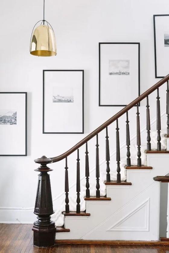 Fotowand im Treppenhaus symmetrische Hängung einer Linie entlang angeordnet kleine Bilder weißer Hintergrund dünne schwarze Rahmen