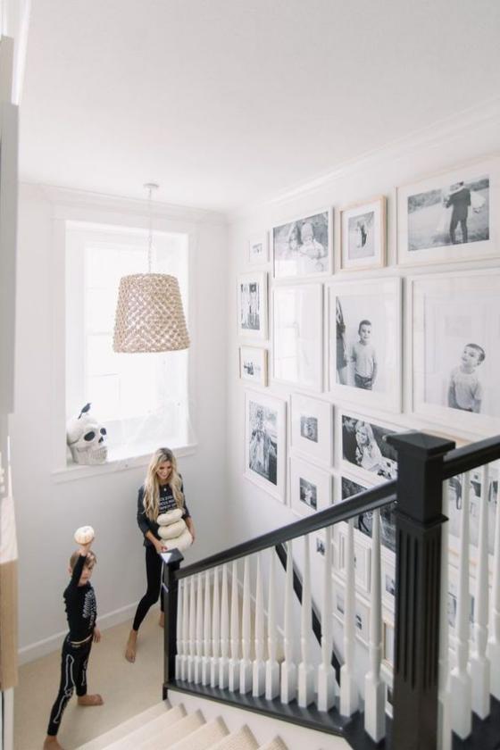 Fotowand im Treppenhaus viele Bilder in weißen Rahmen Mutter Sohn auf der Treppe
