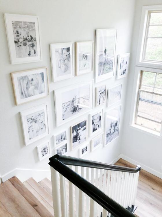 Fotowand im Treppenhaus viele Bilder in weißen Rahmen viel Tageslicht schöne Gestaltung