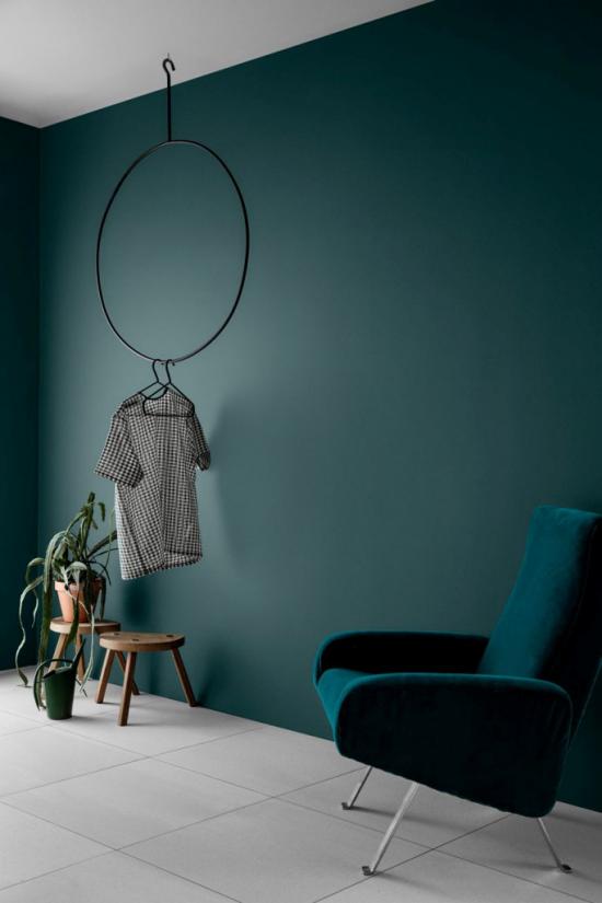 Mehr Farbe ins Interieur bringen gesättigte Farben Dunkelblau Wand Sessel grauer Boden starke optische Ausstrahlung