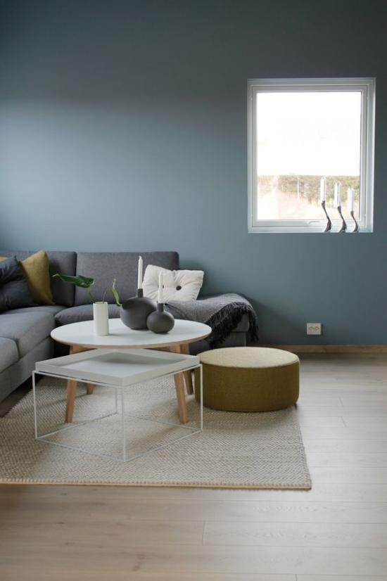 Mehr Farbe ins Interieur bringen heller Teppich graues Sofa blaue Wandfarbe einheitliches Gestaltungskonzept Wohnzimmer