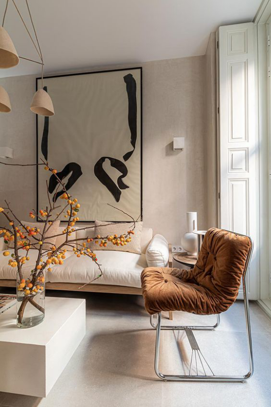 Mehr Farbe ins Interieur minimalistische Raumgestaltung eleganter Sessel in Sandfarbe Tisch Vase mit Zweigen Wanddekoration stilvolles Ambiente