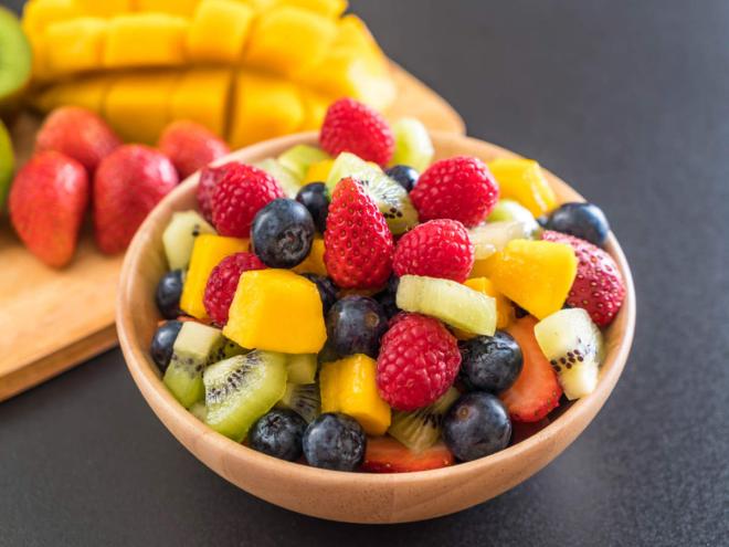Obst essen gesund abnehmen Schale frische Früchte Erdbeeren Blaubeeren Ananas Kiwi in Stücke geschnitten