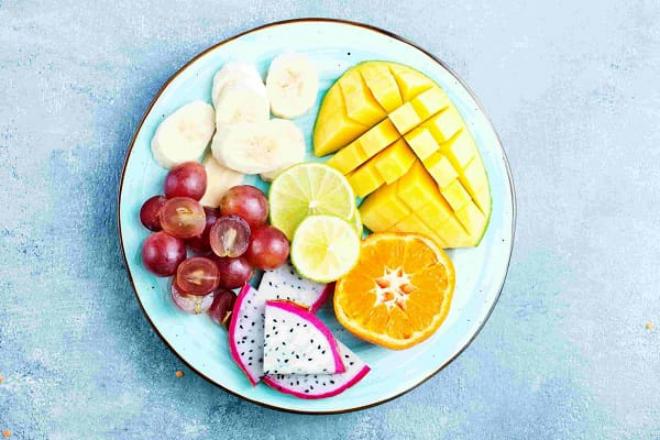 Obst essen gesund abnehmen abends Früchte meiden auf einem Teller Ananas Orangen Banane in Scheiben geschnitten Trauben