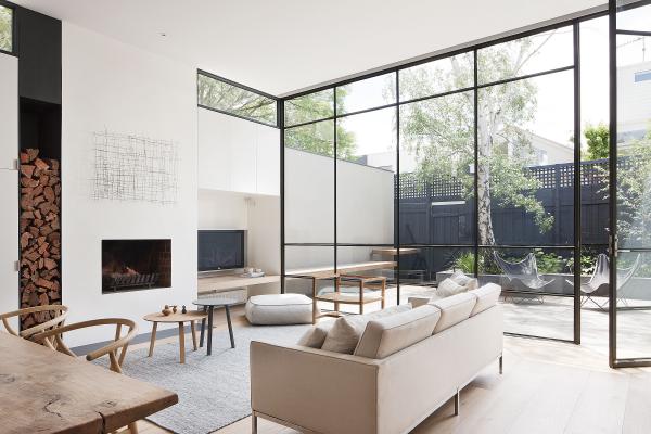 Open-Air-Wohnzimmer deckenhohe Glaswände bequemes Sofa Holztisch Stühle