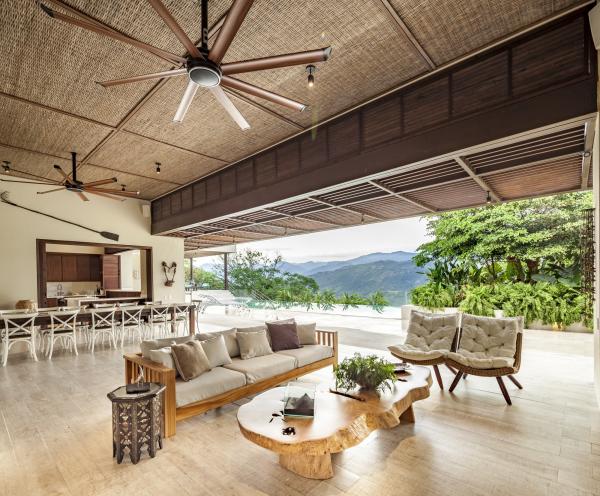 Open-Air-Wohnzimmer großzügiges Raumkonzept Blickfang Kaffeetisch aus Holz zwei Sessel bequemes Sofa im Hintergrund Esstisch viele Stühle