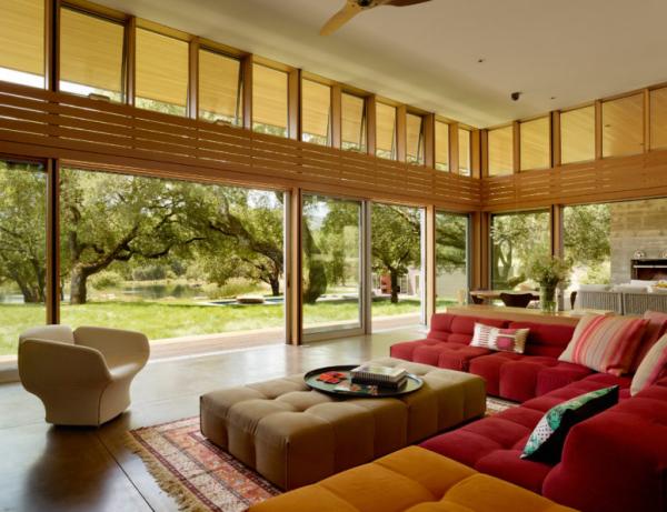 Open-Air-Wohnzimmer hohe Glaswände bequeme Sitzmöbel warme Farben Blick auf den Garten viel Grün draußen