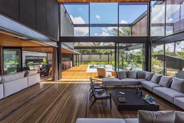 Open-Air-Wohnzimmer luxuriöses Raumkonzept graue Sitzgarnitur dunkler Bodenbelag