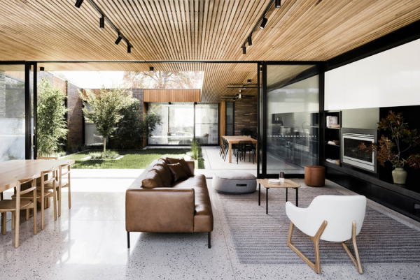 Open-Air-Wohnzimmer luxuriöses Raumkonzept großzügige Gestaltung Bodenbelag graues Mosaik warme Holzfarben viel Grün draußen