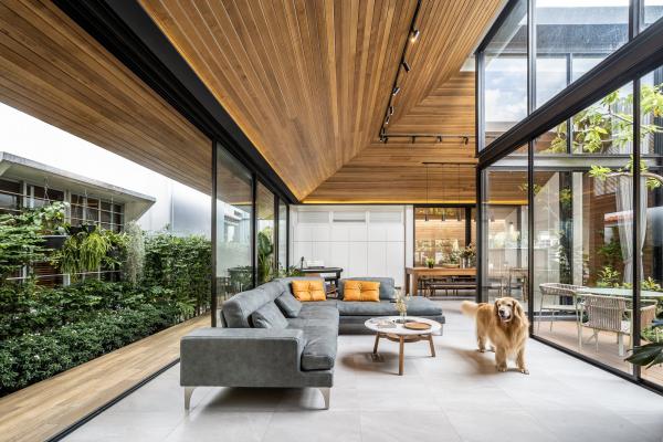 Open-Air-Wohnzimmer vertikaler Garten links bequeme Sitzmöbel deckenhohe Glaswände Hund großzügiges Raumkonzept