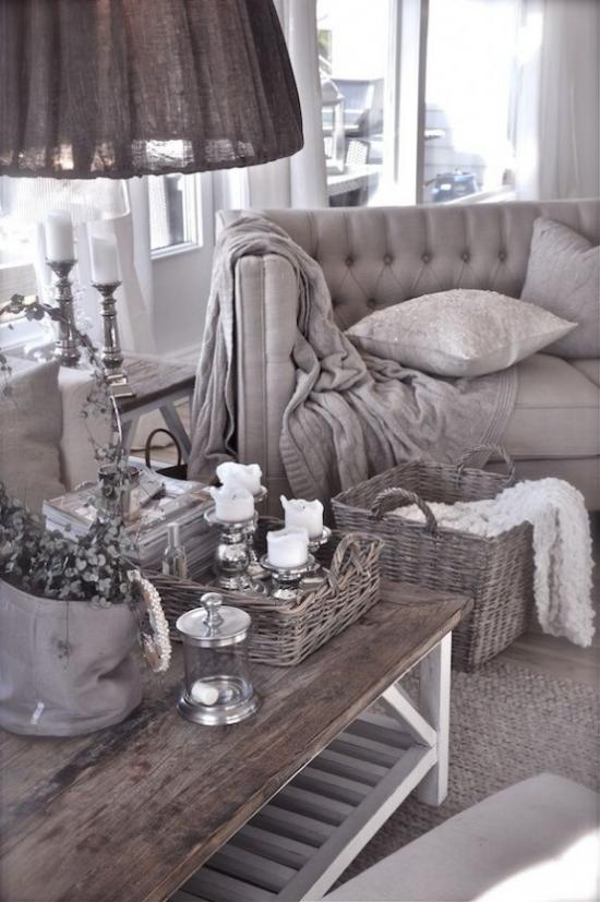 Provence-Stil Grau dominiert Sessel Tisch ländliches Tablett weiße Kerzen dunkle Lampe graue Wurfdecke