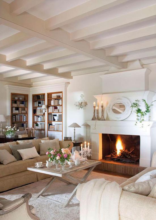 Provence-Stil gemütliches Wohnzimmer helle Farben bequeme Sitzmöbel vor dem Kamin einfacher Tisch Kerzen Blumen Bücherregal im Hintergrund