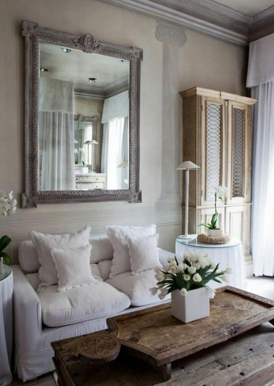 Provence-Stil gemütliches Wohnzimmer romantische Raumgestaltung bequeme Möbel weiße Bezüge Kissen Holztisch weiße Tulpen Wandspiegel