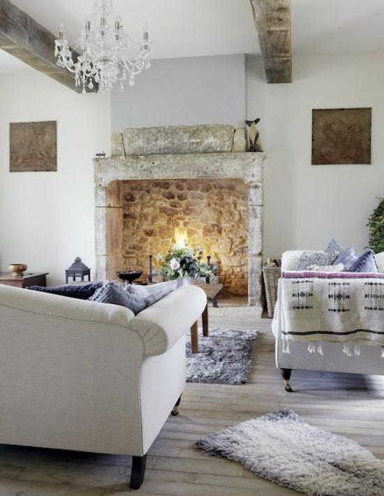 Provence-Stil gemütliches stilvoll gestaltetes Wohnzimmer Sitzgarnitur in hellem Grau Akzente in Lavendel Teppich Kissen Steinkamin