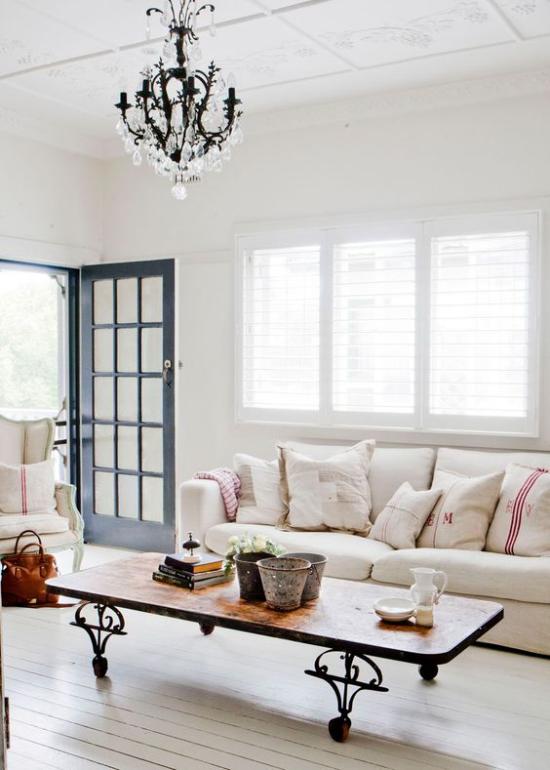Provence-Stil helles lichtdurchflutetes Wohnzimmer einfache Möbel offene Tür kahler Boden