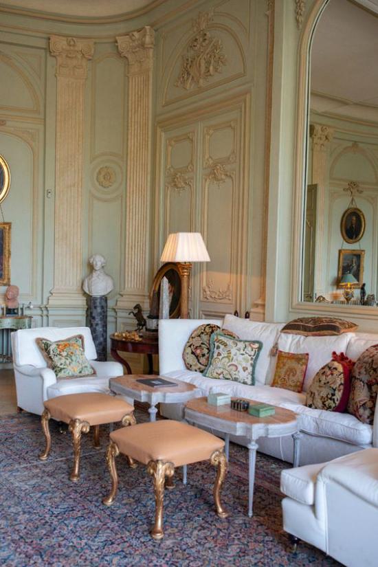 Provence-Stil klassische Einrichtung im Wohnzimmer weiße Sitzmöbel gemusterte Wurfkissen zwei kleine Tische zwei Hocker Lampe
