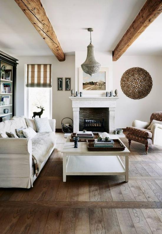 Provence-Stil ländliches Wohnzimmer kahler Boden Holzbalken an der Decke Raumaccessoires aus Naturmaterialien typisch für den französischen Landhausstil