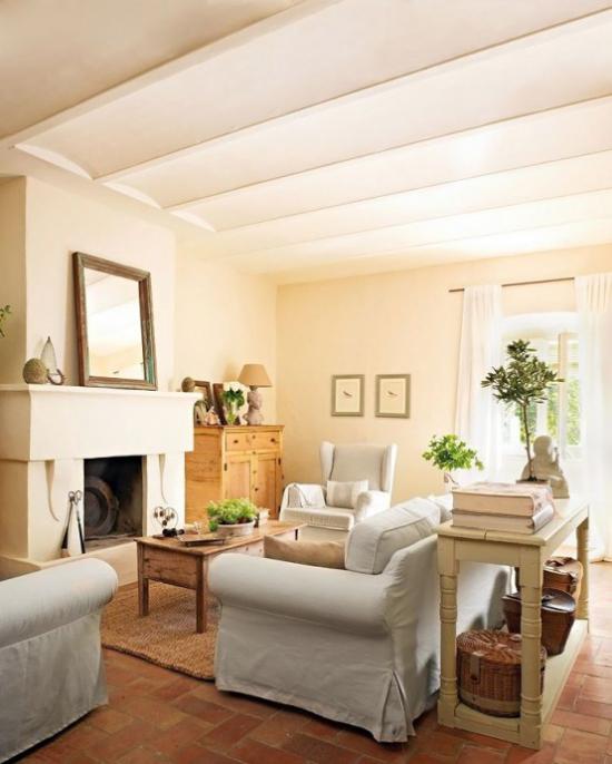 Provence-Stil lichtdurchflutetes Wohnzimmer Sandfarben viel Holz weiße Bezüge der Sitzgarnitur Kamin