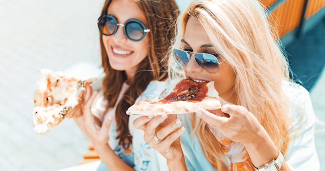 Regel zwei junge Frauen Pizza essen fröhlich sein lachen