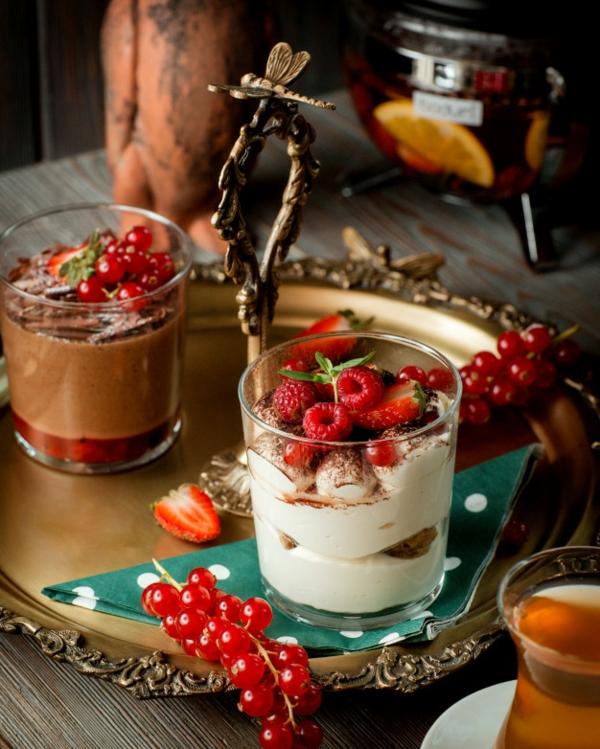 Erdbeer-Tiramisu im Glas Himbeeren und halbierte Erdbeeren