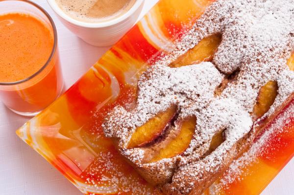 Aprikosenkuchen serviert frischer Geschmack daneben ein Glas Saft und eine Tasse Kaffee