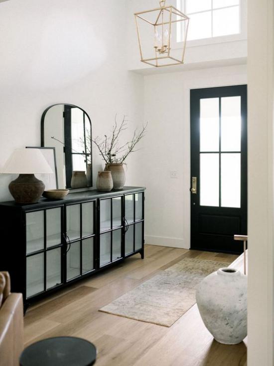 Farbpaare Flur Eingangsbereich in Schwarz und Weiß plus Pastellfarben Läufer schwarze Kommode weiße Wände Vase