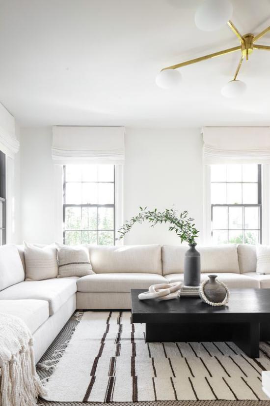 Farbpaare gemütliches Wohnzimmer weißes Sofa schwarzer Tisch Vase grüne Zweige schwarz-weiß gestreifter Teppich
