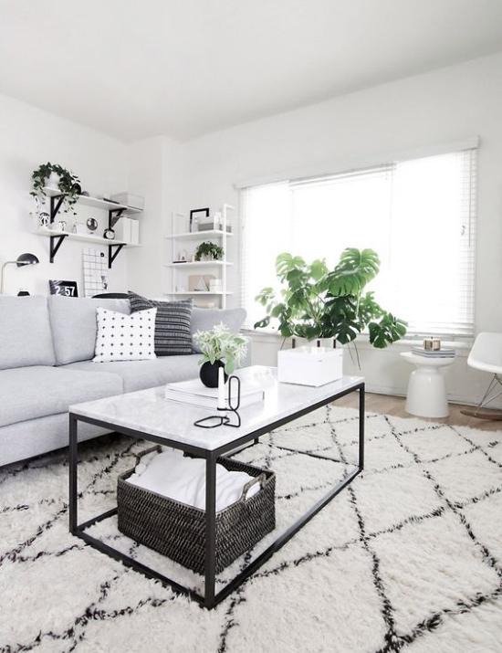 Farbpaare schönes Wohnzimmer in Schwarz und Weiß Sofa Tisch Teppich grüne Topfpflanzen frische Note