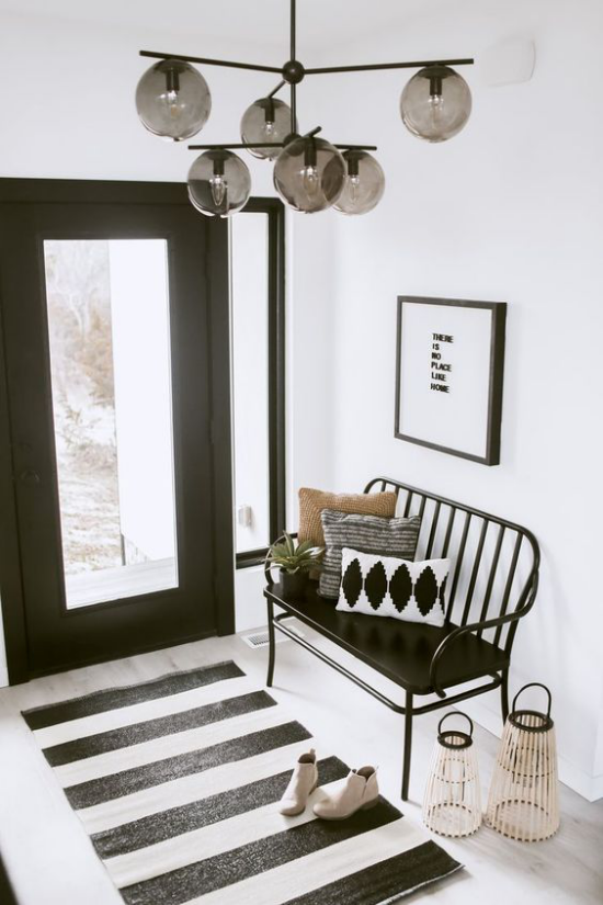 Farbpaare schicke Gestaltung im Flur in schwarz-weiß kleiner Läufer gestreift Sitzbank schwarze Eingangstür