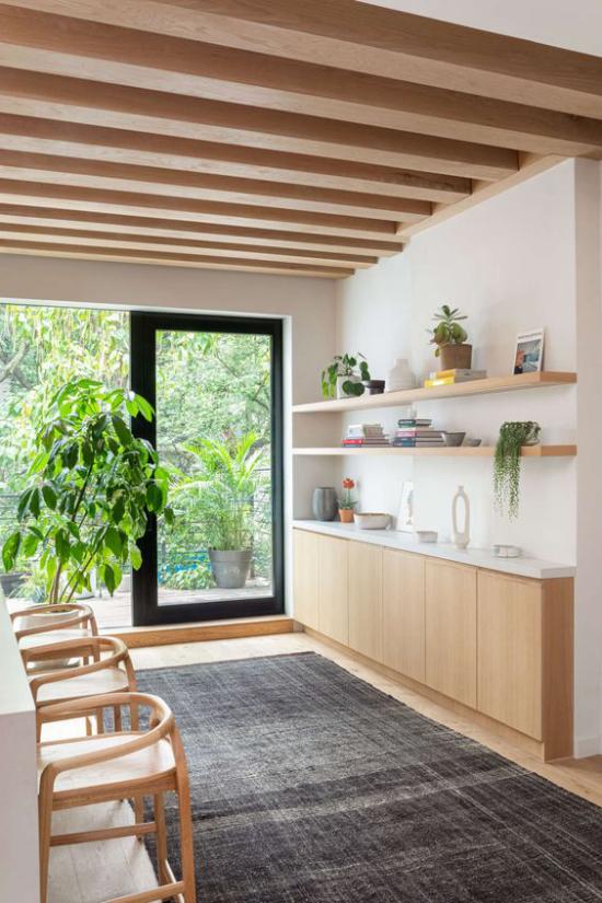 Helles Holz im Interieur Küchenzeile modernes Raumdesign Blick in den Hinterhof viel Grün Holzbalken