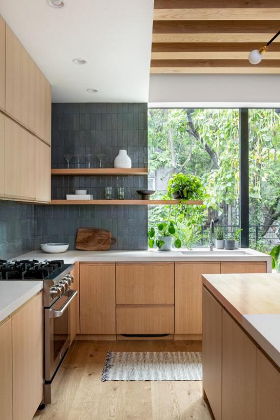 Helles Holz im Interieur moderne Küche Ober-und Unterschränke Herd Spüle Blick ins Freie viel Grün