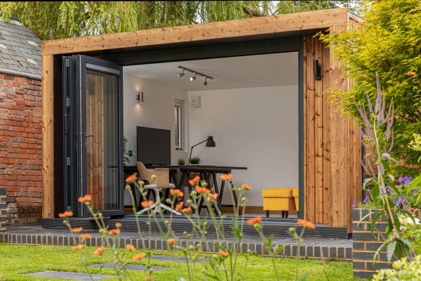 Home Office im Garten moderne Einrichtung drinnen Schreibtisch Bildschirm Tischlampe Stuhl viele bunte Gartenpflanzen draußen ideen