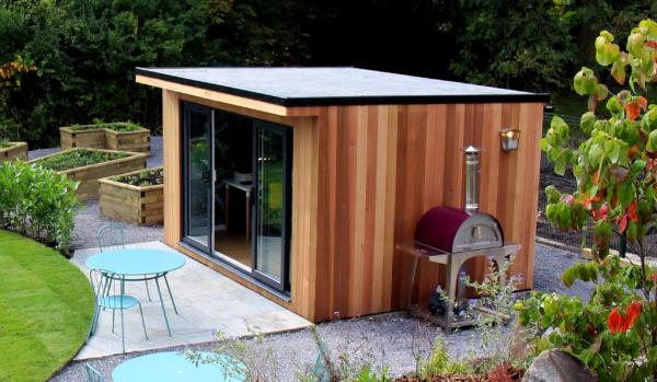 Home Office im Garten schön gepflegter Garten Hochbeete Gartenbüro Tische draußen