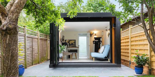 Home Office im Garten schickes Gartenbüro Arbeitsecke PC Schreibtisch Bürostuhl rechts Relax Zone Sofa