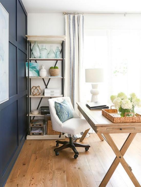 Home Office maritim einrichten Holzboden Schreibtisch weißer Bürostuhl weiße Hortensien dunkelblaue Schränke