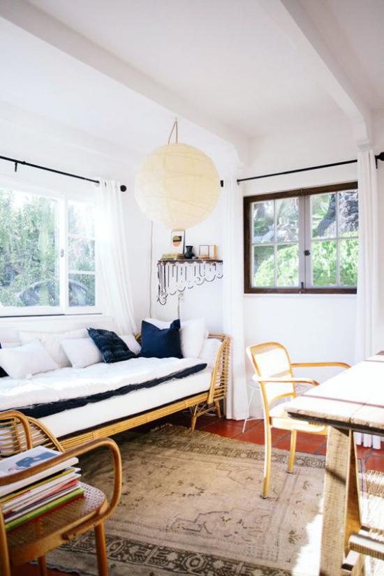 Home Office maritim einrichten einfaches Raumdesign weißes Sofa marineblaue Kissen Teppich Holztisch Stuhl gestapelte Bücher